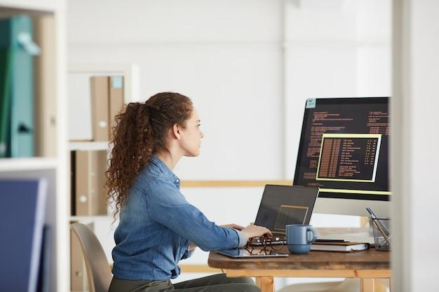 Widok z boku portret żeński programista przy użyciu komputera podczas kodowania w nowoczesnym białym wnętrzu biurowym, miejsce na kopię