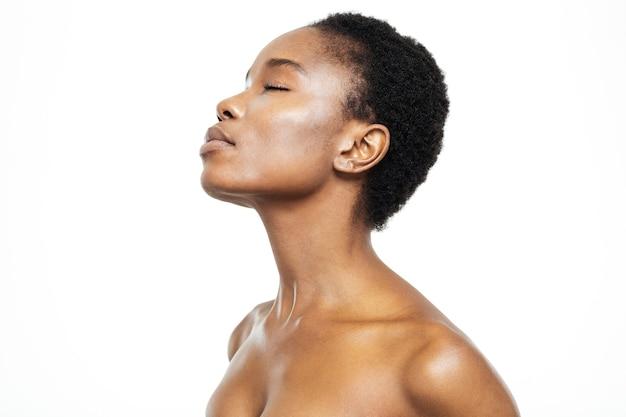 Widok z boku portret zrelaksowanej afroamerykańskiej kobiety stojącej na białym tle na białym tle