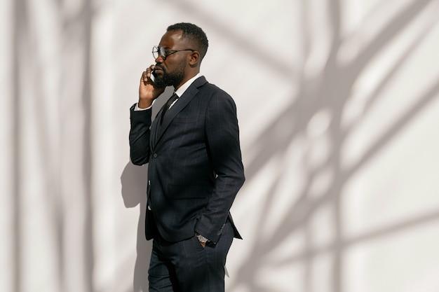 Widok z boku poważnego biznesmena ze smartfonem przez ucho