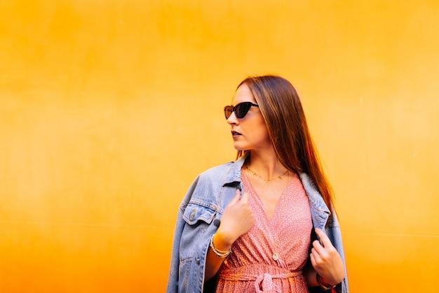 Widok z boku poważnej eleganckiej kobiety w swobodnej różowej sukience, dżinsowej kurtce i niebieskich okularach przeciwsłonecznych dla kota, wyglądających spokojnie i pewnie.