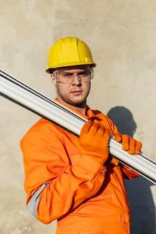 Widok z boku pracownika płci męskiej w kasku i okularach ochronnych