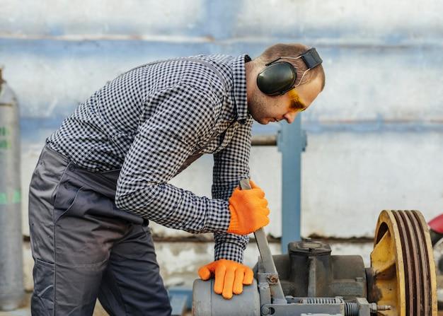 Widok z boku pracownika płci męskiej ze słuchawkami i okularami ochronnymi