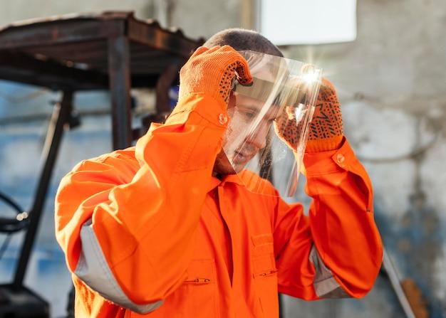 Widok z boku pracownika w mundurze zakładającym osłonę twarzy