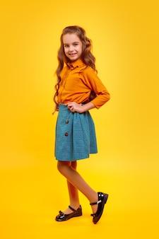 Widok z boku preteen dziewczyna z długimi kręconymi włosami, ubrana w modną bluzkę i stojącą spódnicę, z rękami na talii