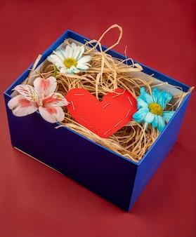 Widok z boku prezentowego pudełka wypełnionego słomą, czerwonym sercem wykonanym z papieru oraz kwiatami stokrotki i alstroemeria na czerwonym stole