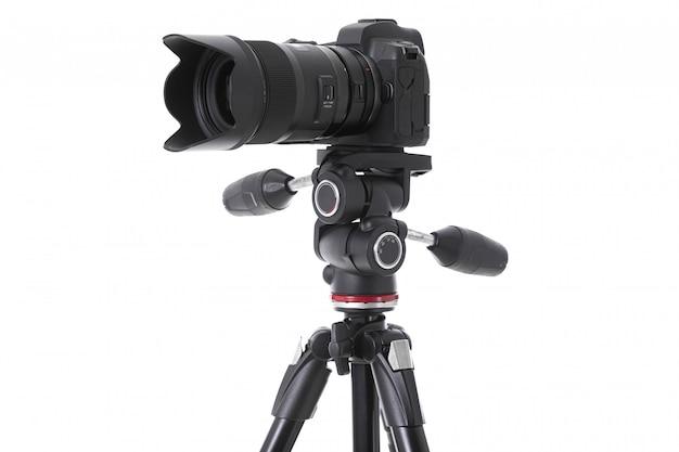 Widok z boku profesjonalnej kamery z dużym szkłem kamery na białym tle