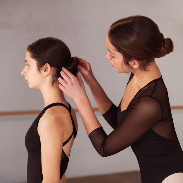 Widok z boku profesjonalnych tancerzy baletowych przygotowujących fryzurę