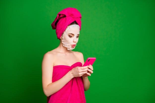 Widok z boku profilu portret nagiej skupionej kobiety noszącej turbanową maskę na twarz za pomocą gadżetów wydętych ust odizolowanych na jasnozielonym tle