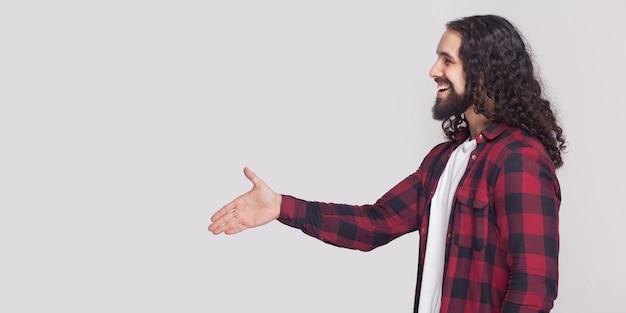 Widok z boku profilu szczęśliwy przystojny mężczyzna z brodą i czarne długie kręcone włosy w kraciastej koszuli stojącej, pozdrowienie z uśmiechem toothy i uściskiem dłoni. kryty strzał studio, na białym tle na szarym tle.
