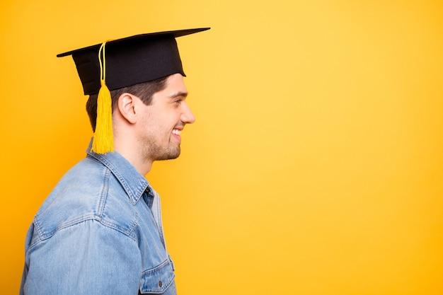 Widok z boku profilu z bliska portret jego miłego, atrakcyjnego, wesołego, zadowolonego faceta w czapce, który uzyskuje specjalistyczny naukowiec na tle jasnego, żywego połysku, żywej żółtej ściany