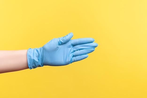 Widok z boku profilu zbliżenie ludzkiej dłoni w niebieskich rękawiczkach chirurgicznych, podając rękę na powitanie lub dotykając.