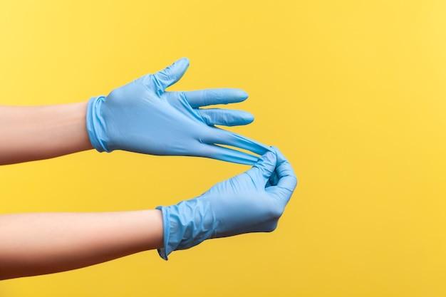 Widok z boku profilu zbliżenie ludzkiej dłoni w niebieskich rękawiczkach chirurgicznych pokazujący, jak zdjąć rękawiczki.