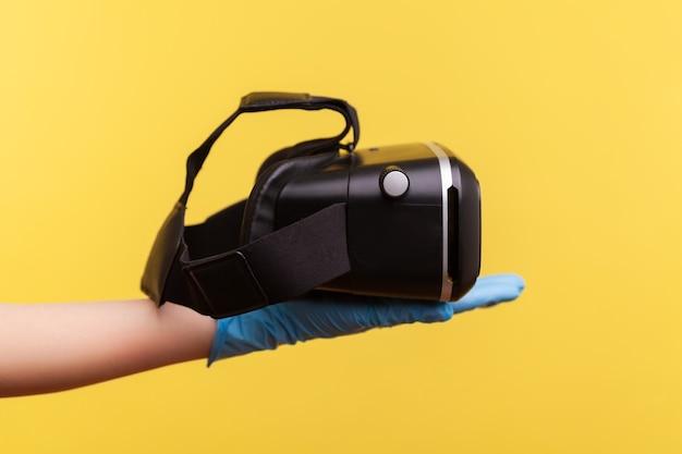 Widok z boku profilu zbliżenie ludzkiej ręki w niebieskie rękawiczki chirurgiczne, trzymając zestaw wirtualnej rzeczywistości.