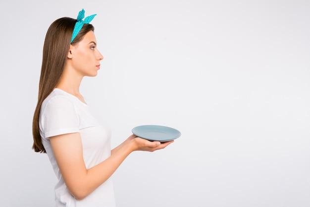 Widok z boku profilu zbliżenie portret miłej spokojnej dziewczyny trzymającej w rękach pusty talerz czekać oczekiwać zamówienia ekologicznego produktu