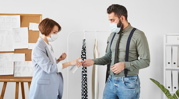 Widok z boku projektantów mody z maskami medycznymi dezynfekującymi ręce przed pracą