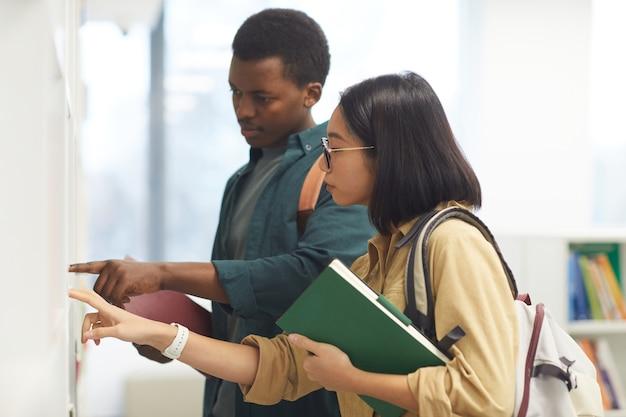 Widok z boku przedstawiający dwóch międzynarodowych studentów wybierających książki na półkach