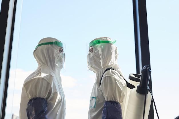 Widok z boku przedstawiający dwóch pracowników dezynfekcji w kombinezonach przeciwgazowych stojących przy oknie i zwróconych ku sobie,
