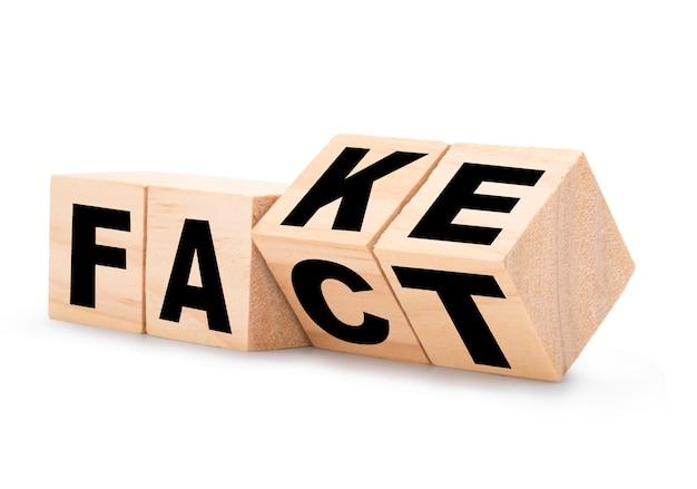 """Widok z boku przewracających się drewnianych kostek do zmiany sformułowań z """"fałszywy"""" na """"fakt"""". na białym tle i ścieżki przycinającej."""