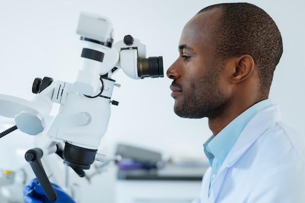 Widok z boku przystojnego młodego dentysty przy użyciu profesjonalnego mikroskopu i potwierdzający diagnozę