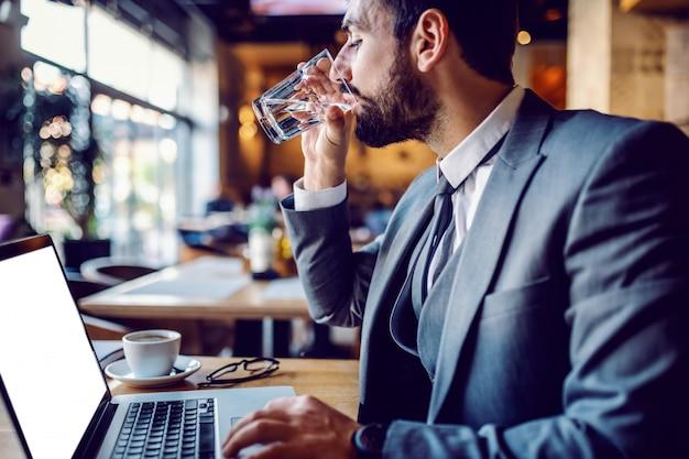 Widok z boku przystojny brodaty biznesmen kaukaski w garniturze siedzi w kawiarni, za pomocą laptopa i wody pitnej.