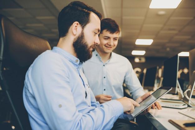 Widok z boku przystojny brodaty mężczyzna przegląda nowoczesny tablet siedząc przy stole w biurze w pobliżu wesoły młody kolega. brodaty mężczyzna za pomocą tabletu w pobliżu kolegi