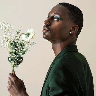 Widok z boku przystojny mężczyzna pozowanie w marynarce i noszenie makijażu trzymając kwiaty