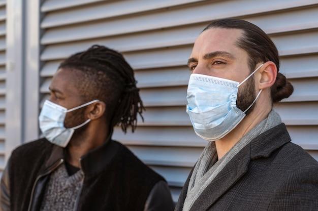 Widok z boku przystojnych mężczyzn noszących maski medyczne