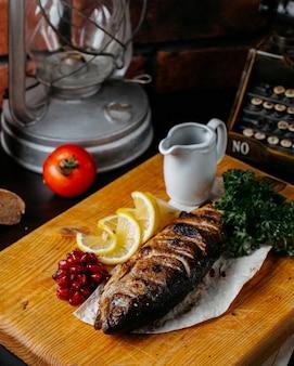 Widok z boku pstrąga z grilla z pestkami cytryny i granatu na drewnianej desce do krojenia