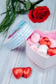 Widok z boku pudełka w kształcie serca wypełnionego różowymi piankami marshmallow i czekoladowymi opakowanymi w czerwoną folię i czerwony kwiat róży na szarym drewnianym stole