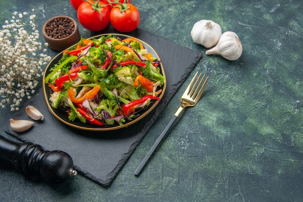 Widok z boku pysznej sałatki warzywnej z różnymi składnikami na czarnej desce do krojenia