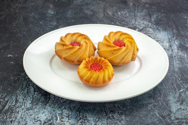 Widok z boku pysznych ciastek na białym talerzu na ciemnej powierzchni
