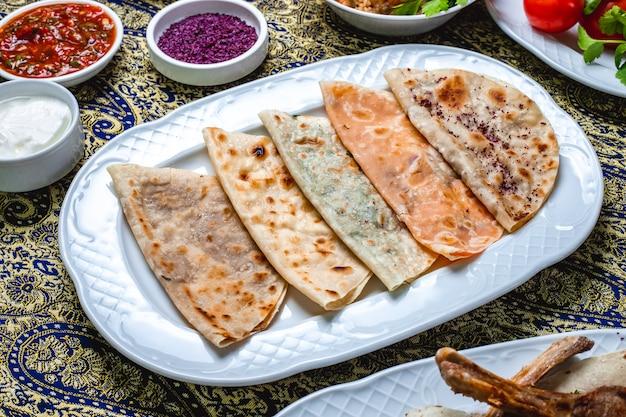 Widok z boku qutab z dyniowym mielonym mięsem, cebulowym serem, sosem pomidorowym, suszonym berberysem i jogurtem na stole