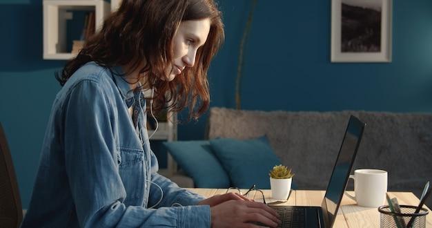 Widok z boku radosnej młodej kobiety za pomocą laptopa siedząc przy biurku w mieszkaniu