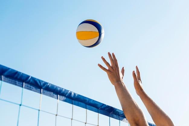 Widok z boku rąk mężczyzny przygotowujących się do uderzenia nad siatką nadlatującą piłkę siatkową