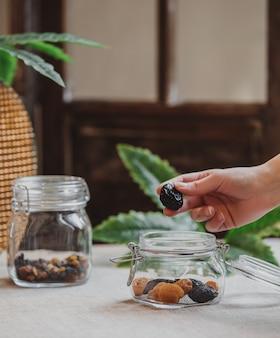 Widok z boku ręcznego suszenia śliwek w szklanym słoju z suszonymi śliwkami