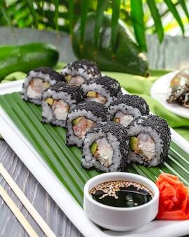 Widok z boku rolki sushi z krewetkami z imbirowym wasabi i sosem sojowym na talerzu