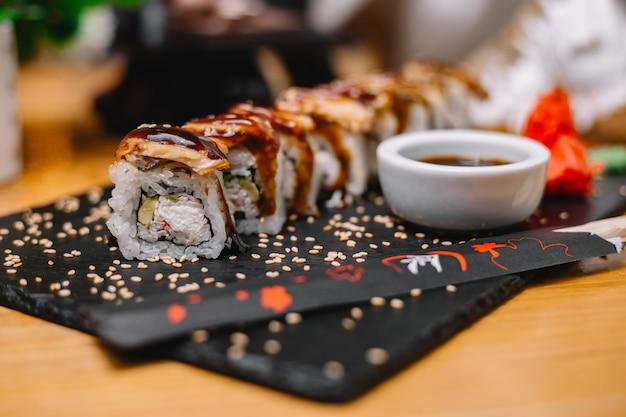 Widok z boku rolki sushi z węgorzem w sosie i sosem sojowym na stojaku
