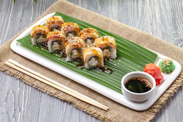 Widok z boku rolki sushi z węgorzem z imbirowym wasabi i sosem sojowym na talerzu