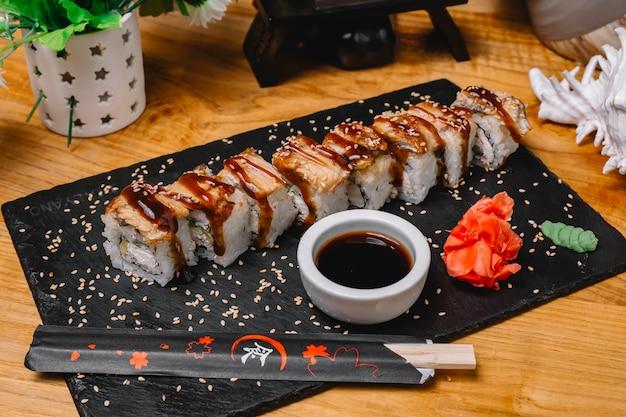 Widok z boku rolki sushi z węgorzem z sosem sojowym i imbirem