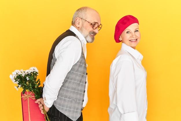 Widok z boku romantycznego, uroczego starszego mężczyzny w eleganckich ubraniach, trzymającego kwiaty i pudełko z prezentami za plecami, który robi niespodziankę stylowej kobiecie, która niczego nie podejrzewa. romans i walentynki