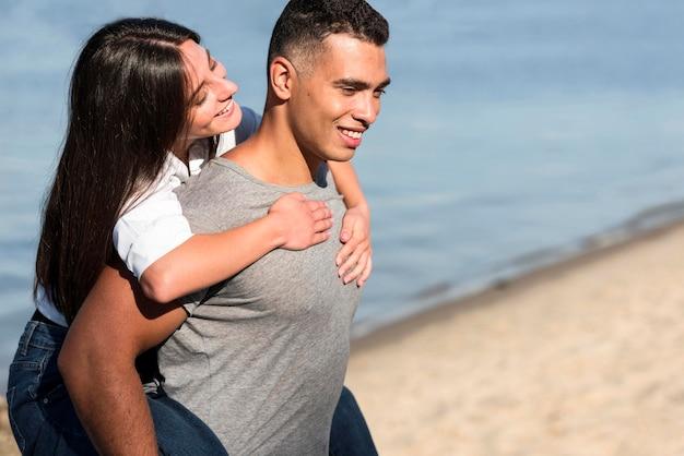 Widok z boku romantycznej pary na plaży z miejsca na kopię