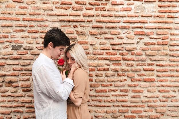 Widok z boku romantycznej pary z różą