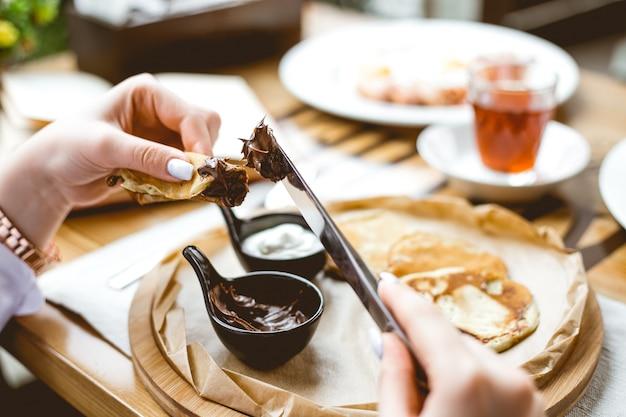 Widok z boku rozmazanego kremu czekoladowego na cienkie naleśniki