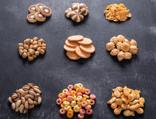 Widok z boku różnego rodzaju przekąsek, takich jak orzechy, krakersy i coockies na ciemnym poziomie
