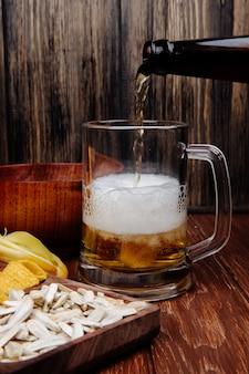 Widok z boku różnych przekąsek słone piwo na drewnianym talerzu i wlewając piwo do kubka na rustykalnym drewnie