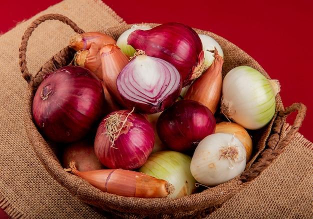 Widok z boku różnych rodzajów cebuli w koszu na worze na czerwonym stole