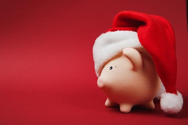 Widok z boku różowej skarbonki z świątecznym kapeluszem na białym tle na jasnym czerwonym tle. akumulacja pieniędzy, inwestycje, usługi bankowe lub biznesowe, koncepcja bogactwa. skopiuj makiety reklamowe.