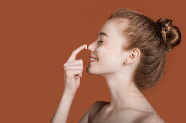 Widok z boku: ruda dama z piegami i nagimi ramionami nakładająca krem na nos i uśmiech, reklama na brązowej ścianie z wolną przestrzenią