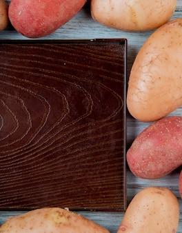 Widok z boku rudych i czerwonych ziemniaków ustawionych w kwadratowy kształt wokół pustej tacy na drewnianym stole