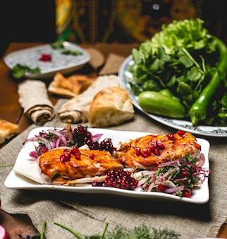 Widok z boku rybny kebab na chlebie pita z granatem i cebulą z ziołami